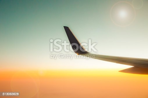 484616224 istock photo Airplane Wing in Flight from window, sunset sky 513063628