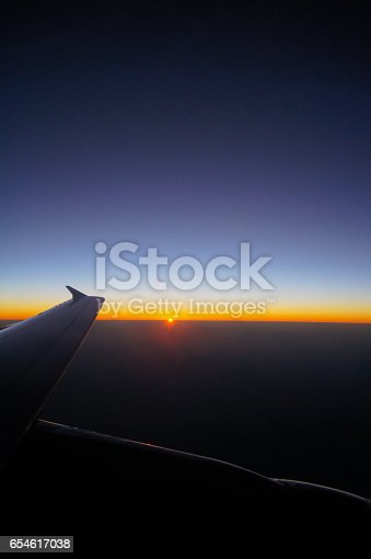 484616224 istock photo Airplane Wing in Flight from window, sunset sky 654617038