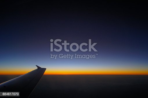 484616224 istock photo Airplane Wing in Flight from window, sunset sky 654617070