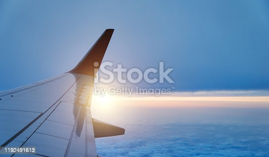 155439315 istock photo Airplane wing in flight on sunset, view from window 1192491613