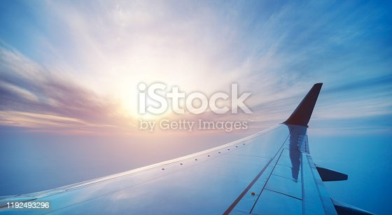 155439315 istock photo Airplane wing in flight on sunset, view from window 1192493296