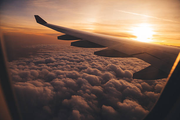 Airplane Wing in Flight view from airplane in flight with sunset altocumulus stock pictures, royalty-free photos & images