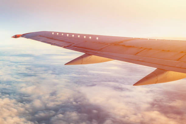 Airplane wing in sky with clouds and sun shine. stock photo