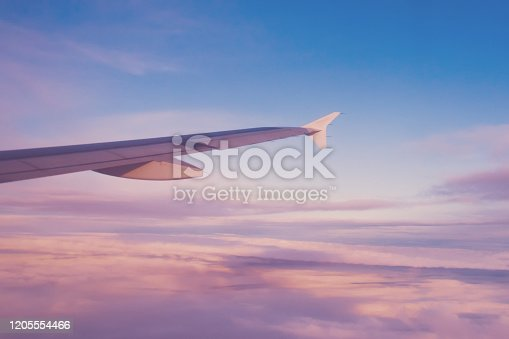 1045890176 istock photo Airplane wing of the setting sun in blue and pink colors. 1205554466