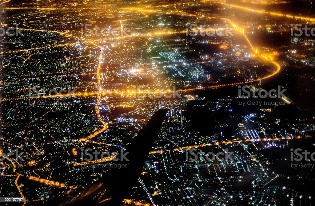 airplane wing over a city illuminated stock photo
