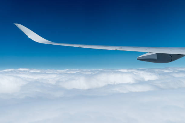 airplane wing over a cloud carpet stock photo