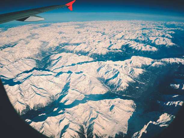 Airplane wing over snow capped sharp winter mountains stock photo