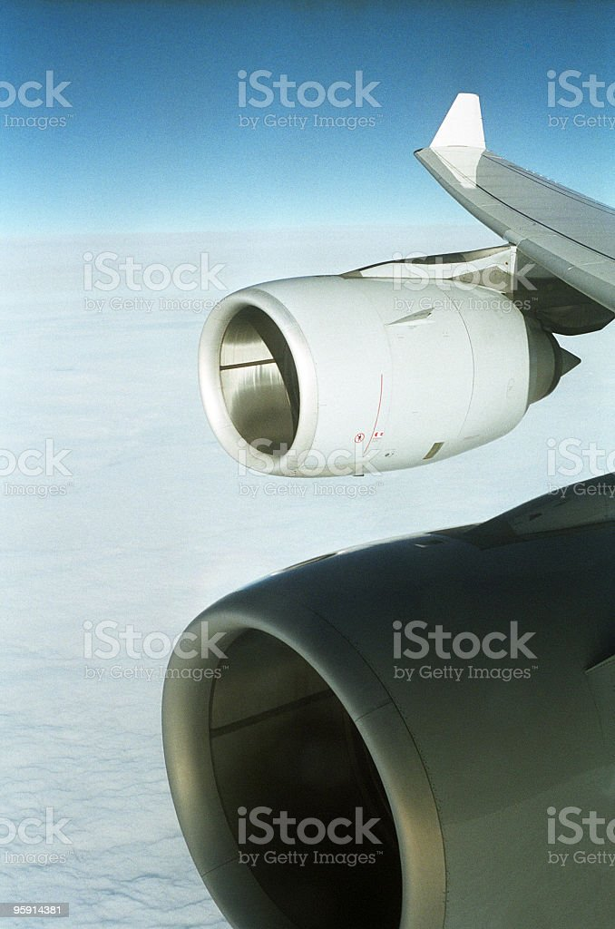 Airplane wing with engines before blue sky and white clouds. royalty-free stock photo