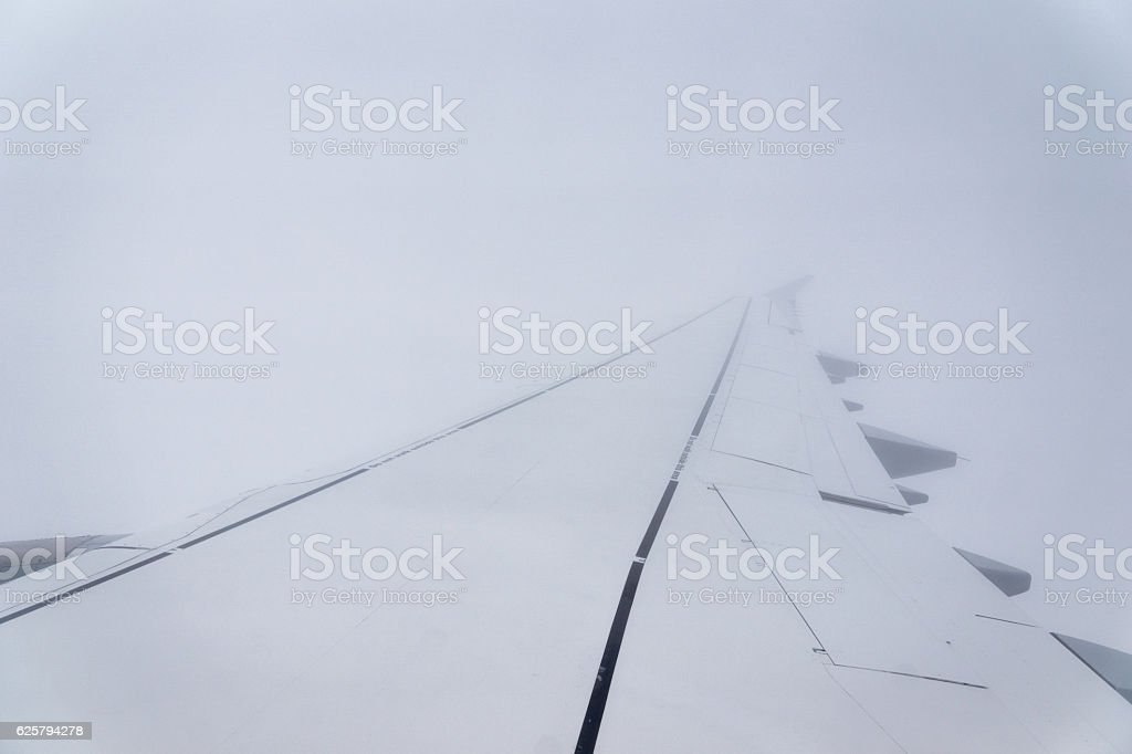 Airplane wingview in adverse weather conditions stock photo