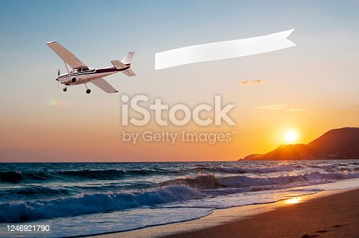 Airplane with banner against sunset background