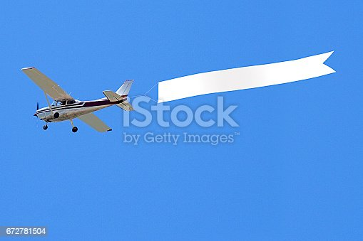 Airplane with banner against sky background
