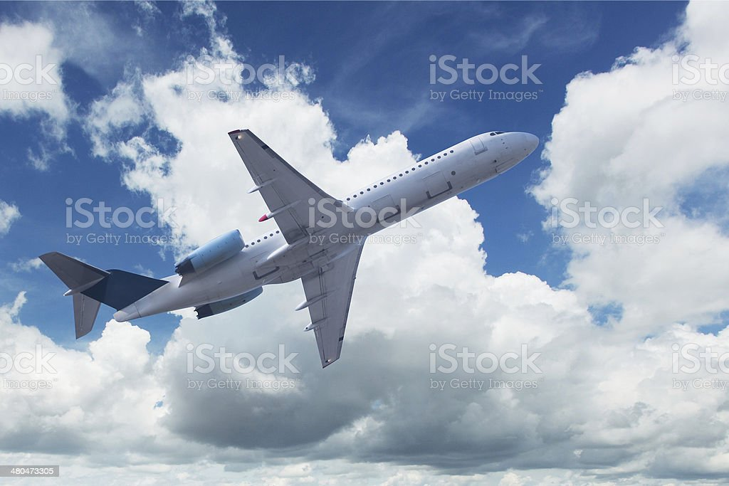Airplane with cumulus clouds stock photo