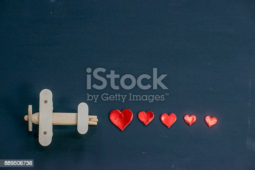 A wooden toy airplane is moving to the side and leaving a trail of red hearts behind it. The background is navy blue.