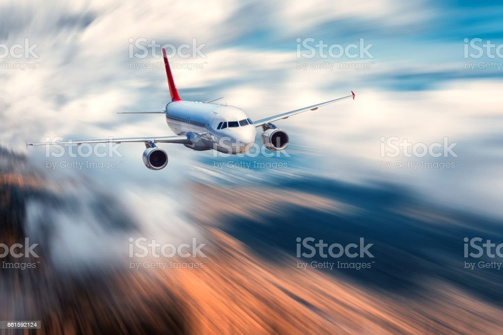 Airplane with motion blur effect. Landscape with flying passenger airplane and blurred background with sky with low clouds, orange forest at sunset. Passenger airplane is landing. Commercial aircraft stock photo