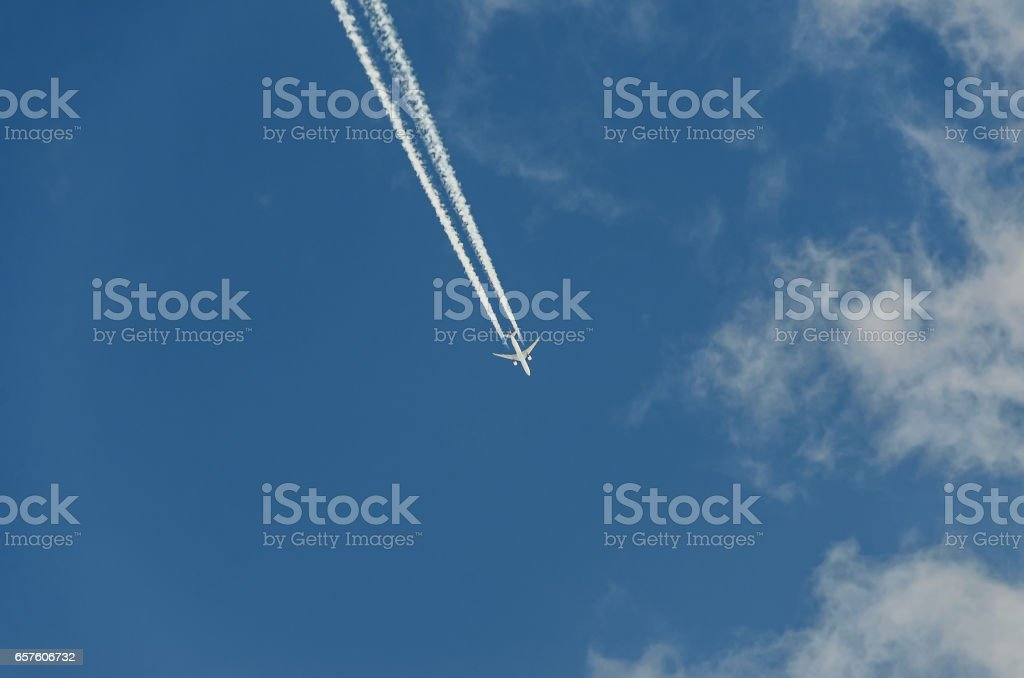 Airplane with reaction trail flying over blue sky with clouds, close up stock photo