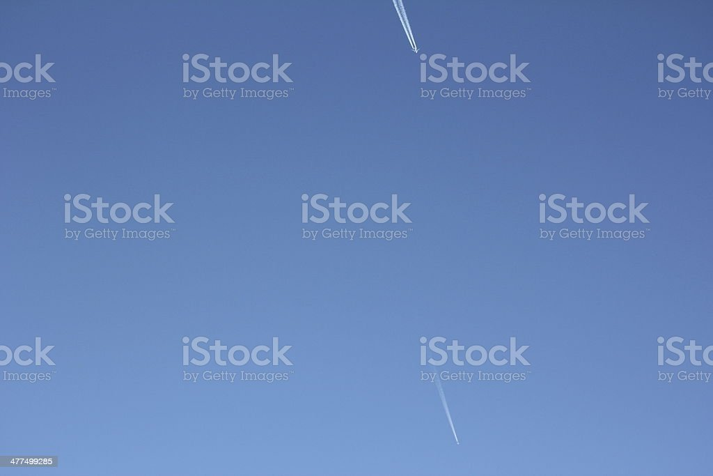 Airplane with Vapor Trail in the Blue Clear Sky royalty-free stock photo