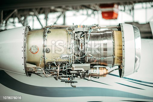 Jet engine on an airplane's right side with it's cover panel removed for maintenance.
