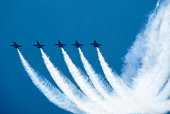 Five fighter jets flying in formation