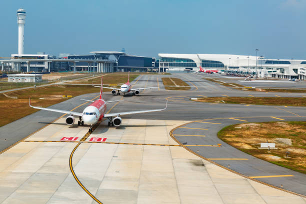 Airplanes in Kuala Lumpur International Airport terminal KLIA 2, Malaysia Kuala Lumpur: Low cost airline Air asia aircrafts waiting for take off on the background of transit passenger terminal building in malaysian international airport KLIA 2 kuala lumpur airport stock pictures, royalty-free photos & images