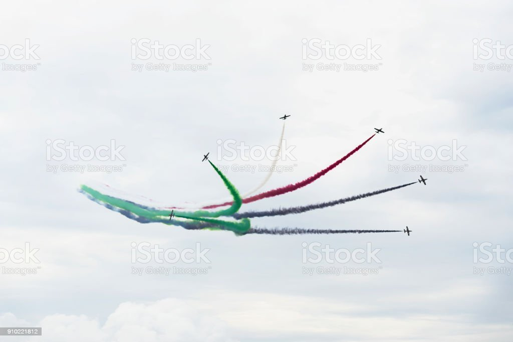 Airplanes on aerobatic show, bright multicolor smoke trails. Aircrafts, flying display, aerobatics, teamwork stock photo