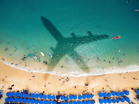 istock Airplane's shadow over a crowded beach 621821582
