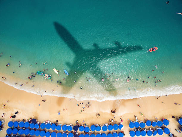 airplane's shadow over a crowded beach - travel destinations stock photos and pictures