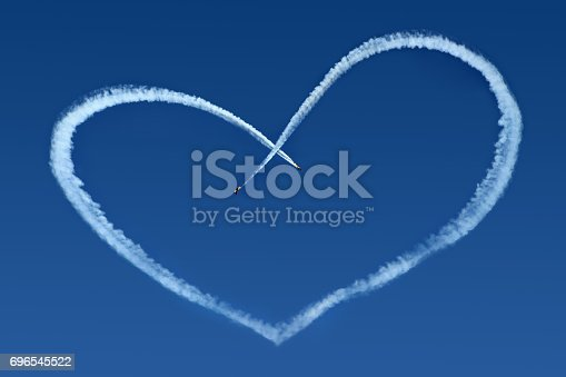 istock Airplanes Skywriting a Heart on blue sky 696545522