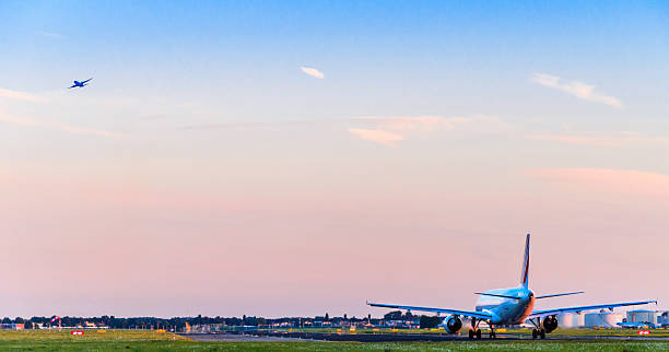 airplanes taking off at sunset - schiphol stockfoto's en -beelden