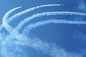 Two airplanes with smoke trails in the blue sky during air show