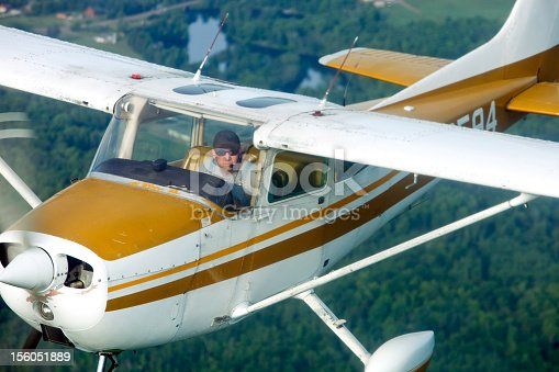 A classic airplane is flying over a wooded area with a lake in the background. Shot from another airplane at a close distance.