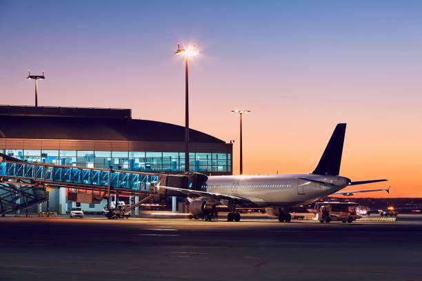 luchthaven bij de kleurrijke zonsondergang - luchthaventerminal stockfoto's en -beelden