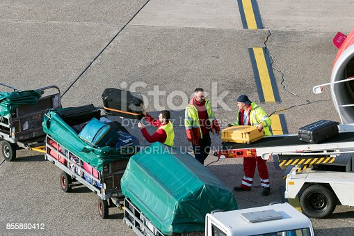 Baggage handlers unloading luggage from an airplane at Dusseldorf airport.