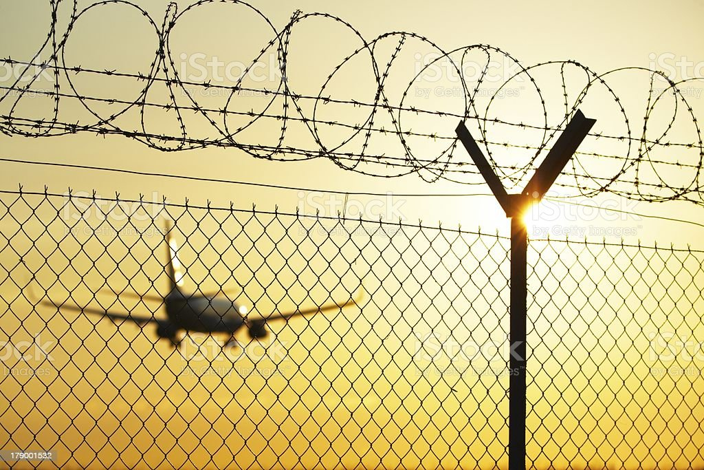 Airport behind guard fence in sunset stock photo
