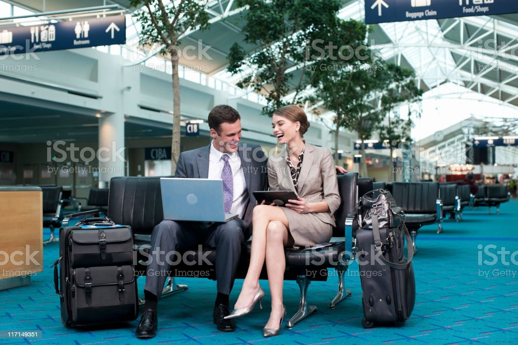 Airport Business Travel, Coworkers Using Laptop in Waiting Area royalty-free stock photo
