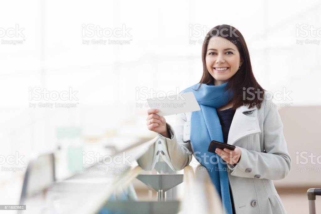 Airport business woman with smart phone at gate waiting in terminal stock photo