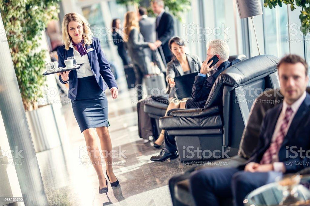 Airport cafe waitress bringing coffee stock photo