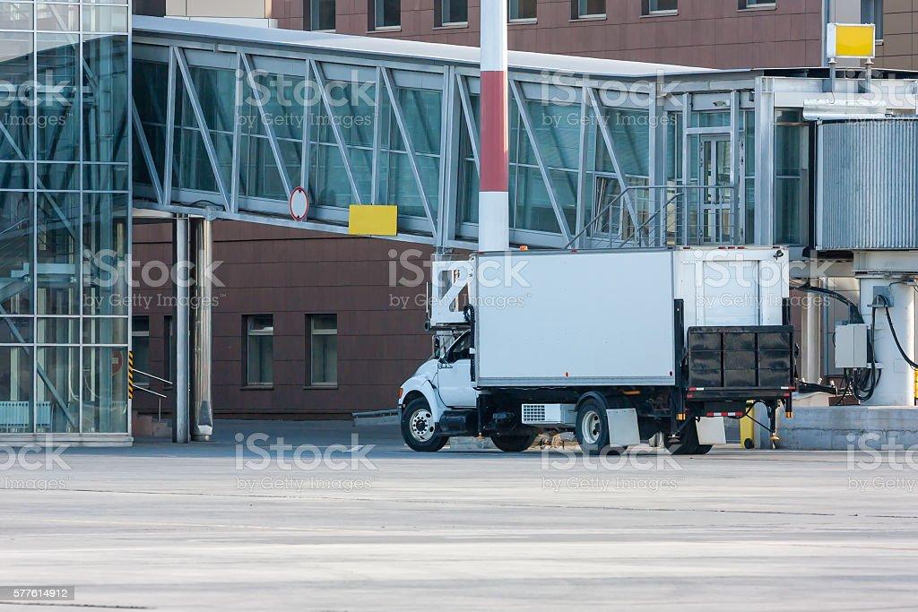 Airport catering truck near passenger boarding bridge стоковое фото
