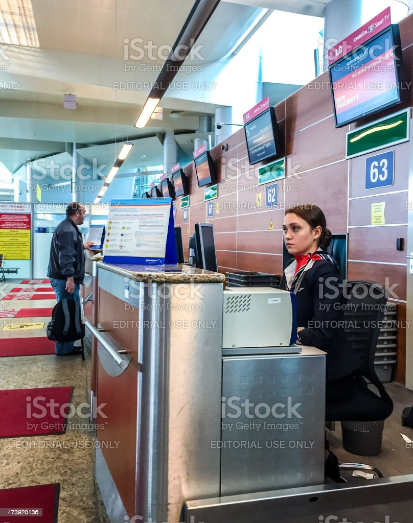 Airport Check-in Attendant waiting for passengers stock photo