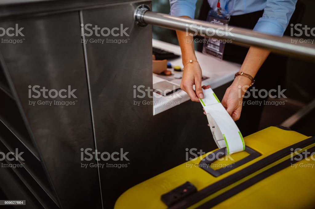 Airport check-in counter employee attaching tag on luggage stock photo