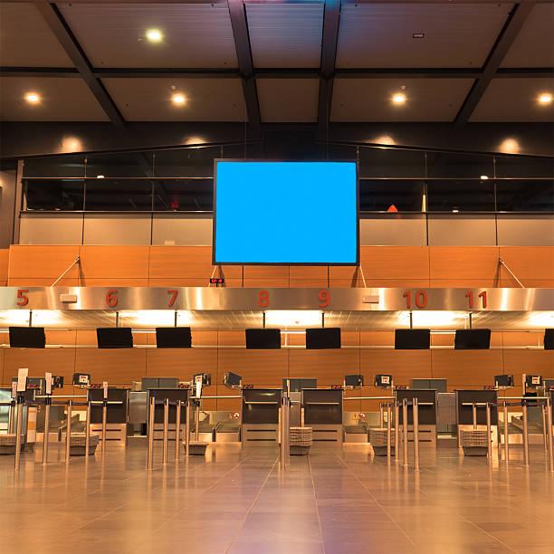 Os balcões de Check-in do aeroporto no Terminal - foto de acervo