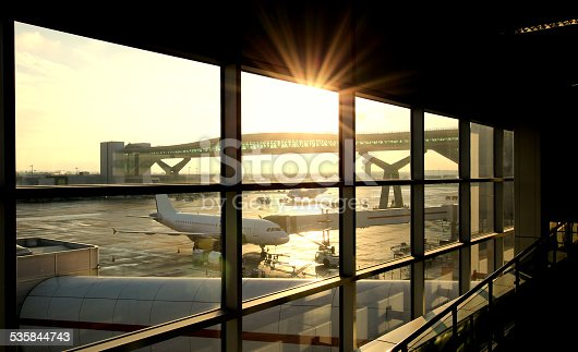 Airport departure lounge with passenger plane being loaded.