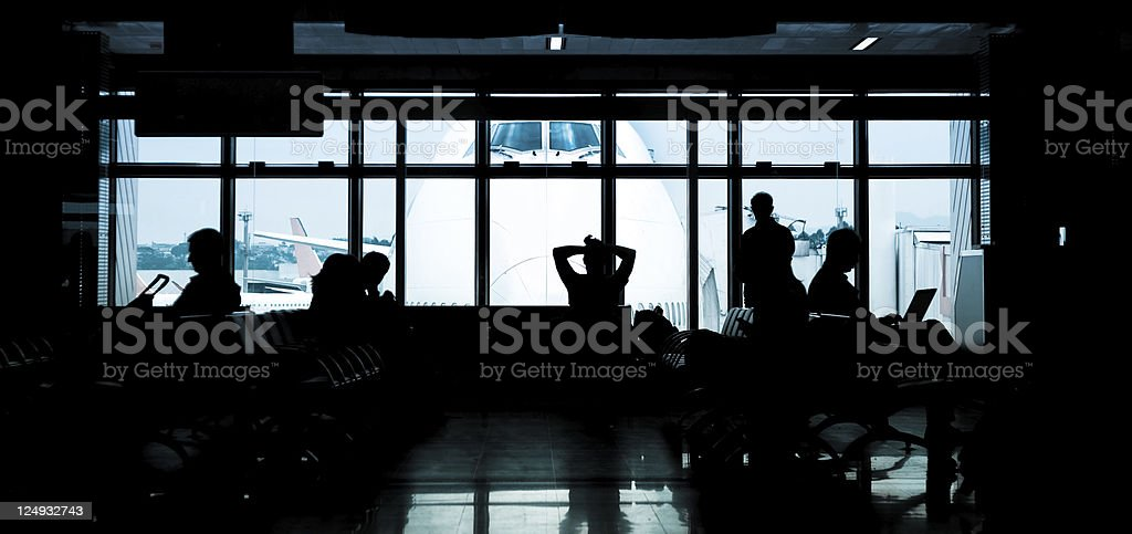 Airport gate, unrecognisable people waiting, airplane outside royalty-free stock photo
