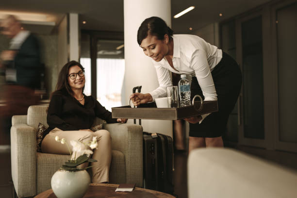 Airport lounge waitress serving coffee to female passenger stock photo