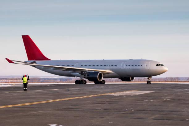 Flughafen Marshaller trifft Passagier-Jet-Flugzeug, das Taxizum Parkplatz bei kaltem Winterwetter – Foto