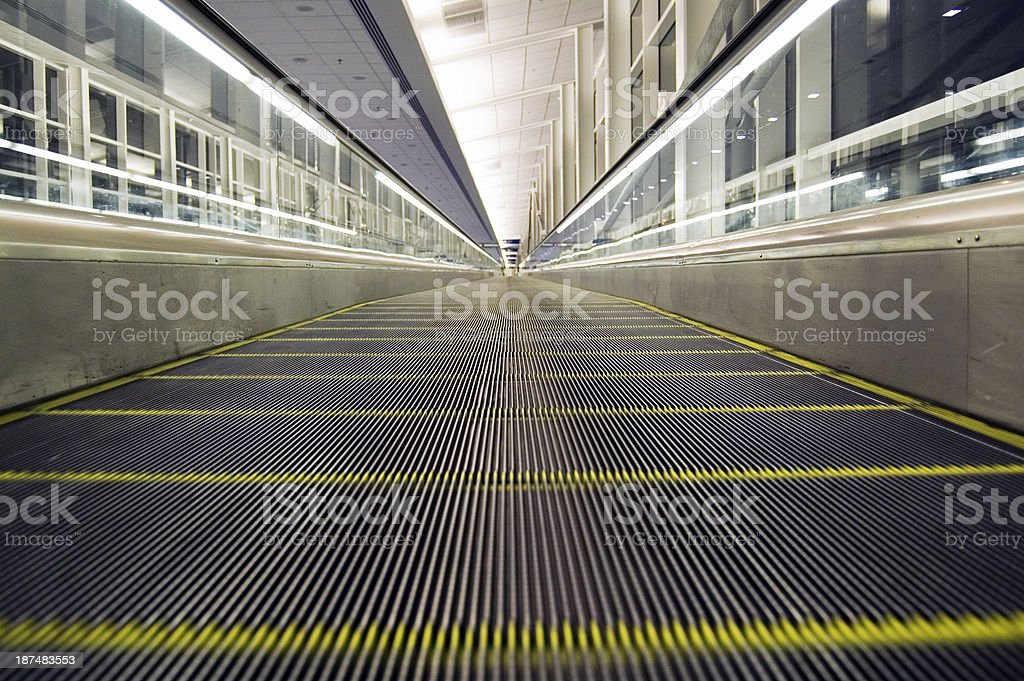 Low angle view of an empty airport moving walkway at night....