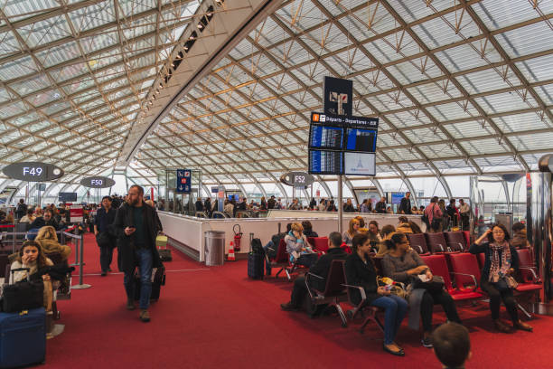 CDG Airport, Paris - 12/22/18: People passengers waiting to board CDG Airport, Paris - 12/22/18: People passengers waiting to board on their international flights. Hand luggage, families, kids. val d'oise stock pictures, royalty-free photos & images