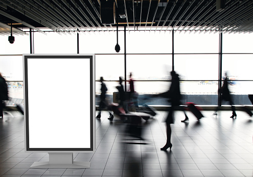 Airport passengers crowd walking blurred people billboard advertisement