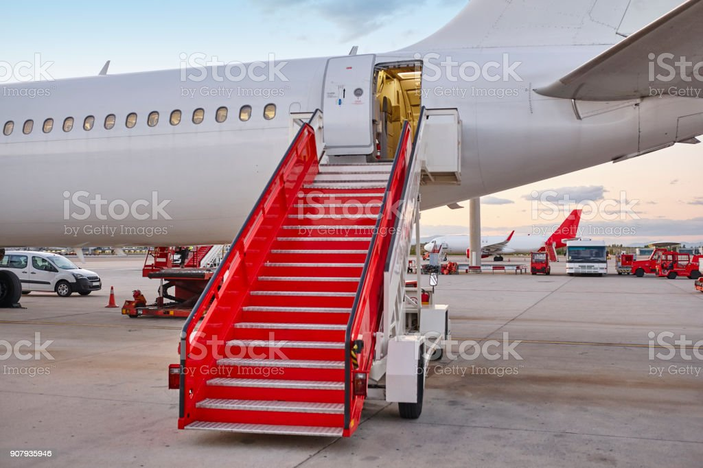 Airport runaway with airplane and stairway. Travel background. stock photo