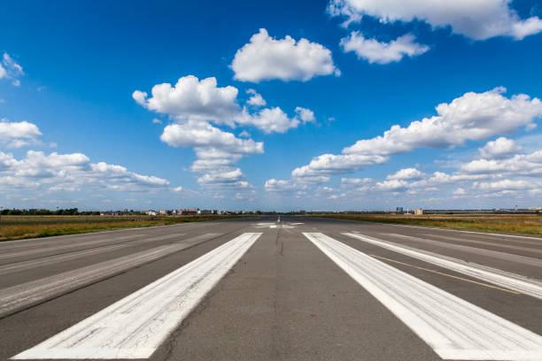 de landende stroken van de luchthavenbaan tegen bewolkte blauwe hemel - vliegveld stockfoto's en -beelden