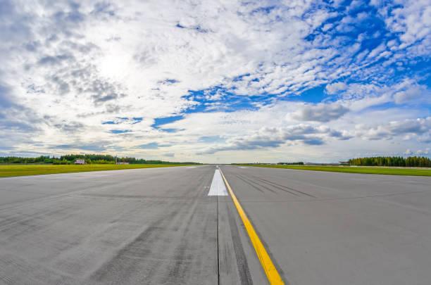 de startbaan van de luchthaven naar in horizon en pittoreske wolken in de blauwe hemel. - vliegveld stockfoto's en -beelden